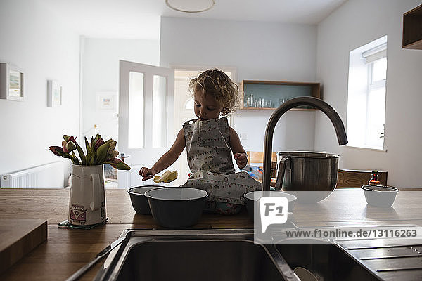 Girl with food sitting on kitchen counter