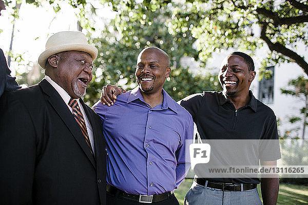 Glücklicher Vater spricht mit Söhnen  während er im Park an Bäumen steht