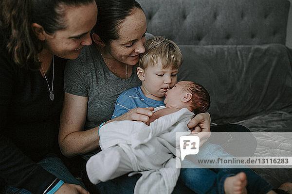 Lesbische Mütter  die den Sohn ansehen  der den Bruder küsst  während sie zu Hause im Bett sitzen