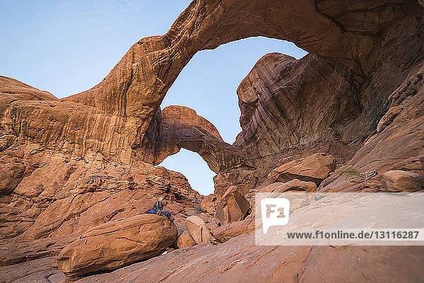 Niedrigwinkelansicht einer Frau  die auf einer Felsformation im Arches-Nationalpark gegen den Himmel sitzt