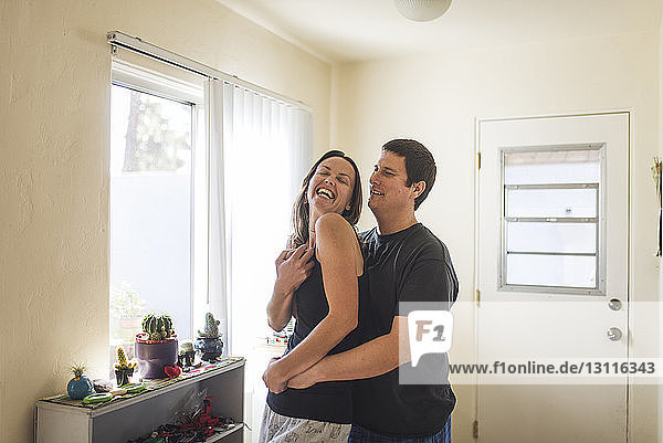 Happy couple standing by window at home