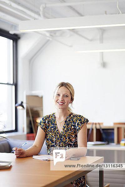 Porträt einer lächelnden Geschäftsfrau  die im Büro am Tisch sitzt