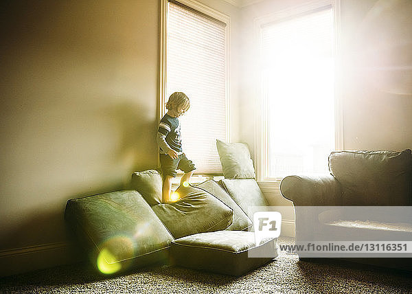 Boy standing on cushions at home