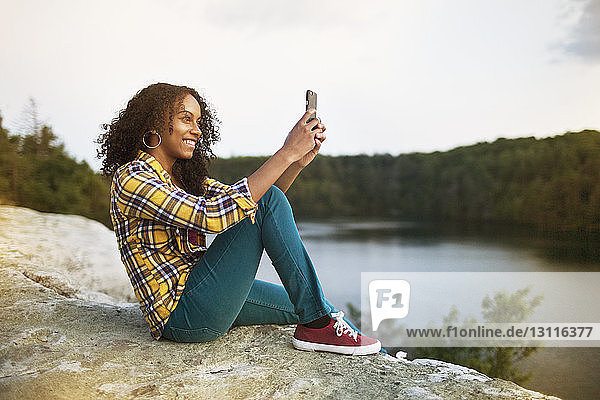 Happy woman taking selfie through smart phone on rock by lake