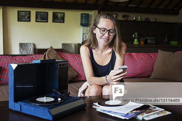 Smiling woman using phone while listening music record at home