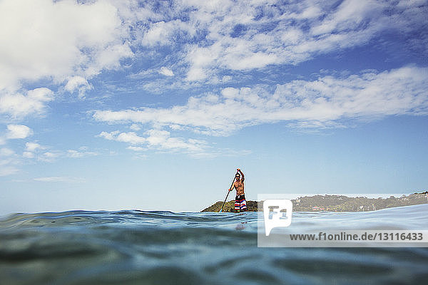 Man paddleboarding in sea against sky