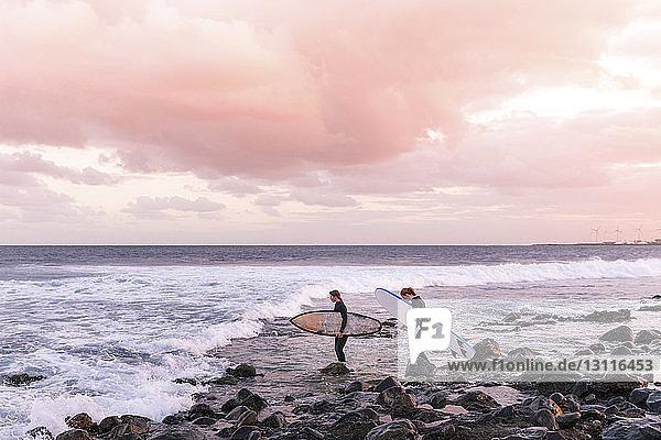 Freundinnen tragen Surfbretter an Land am Strand gegen bewölkten Himmel