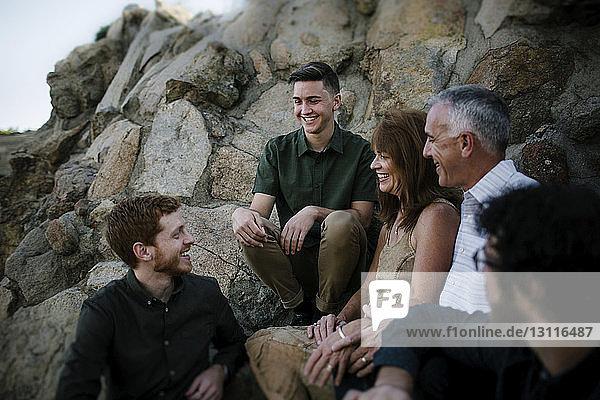 Glückliche Eltern unterhalten sich mit ihren Söhnen  während sie bei Felsformationen im Park sitzen