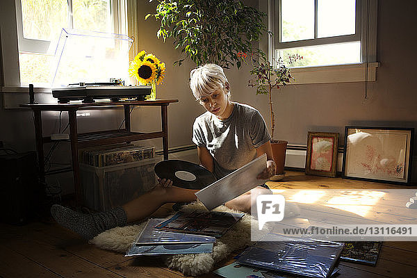 Young woman looking at vinyl records while sitting on floor at home