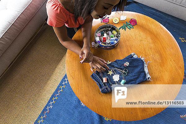 Hochwinkelansicht einer Frau  die sternförmige Textilpatches auf Jeans am Tisch anpasst