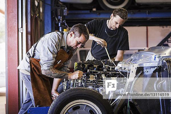 Mechaniker reparieren Automotor in Autowerkstatt