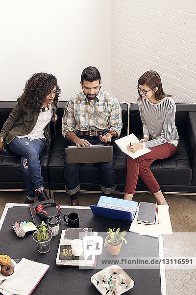 Hochwinkelansicht von Geschäftsleuten mit Laptop im Büro