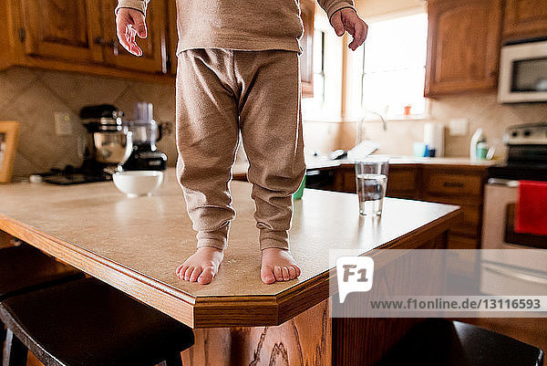 Low section of boy standing on wooden table in kitchen