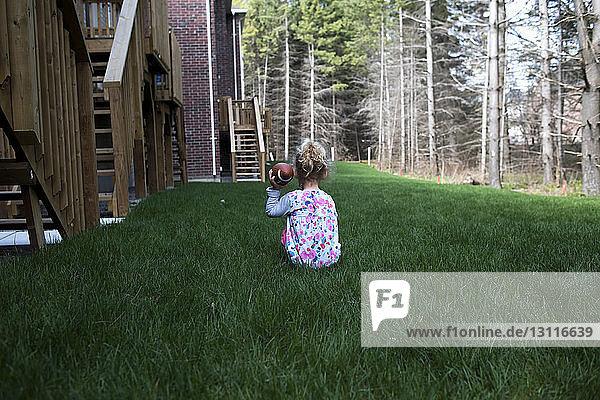 Rückansicht eines Mädchens  das American Football hält  während es auf einem Rasenfeld im Hof sitzt