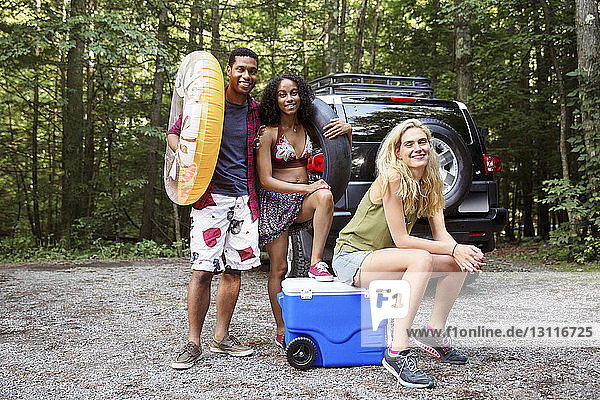 Portrait of friends with inflatable rings and cooler in forest