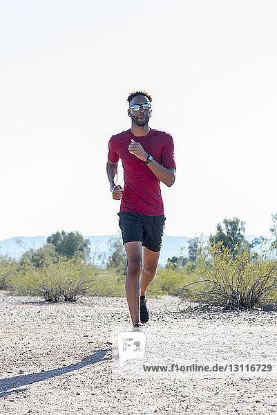 Männlicher Wanderer mit Sonnenbrille beim Laufen auf dem Feld gegen den klaren Himmel am sonnigen Tag
