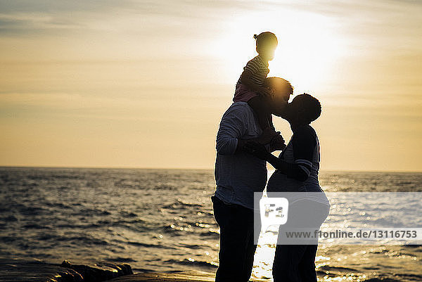 Silhouette man kissing wife while carrying daughter on shoulders at beach during sunset