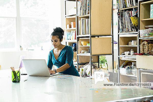 Selbstbewusste Geschäftsfrau  die am Laptop-Computer am Tisch im Büro arbeitet