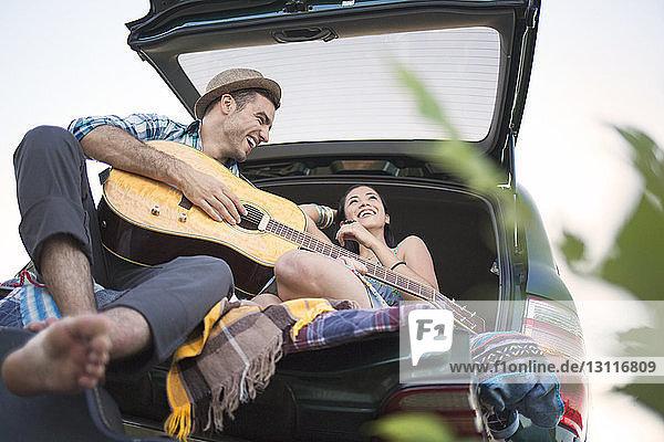 Niedriger Blickwinkel auf ein lachendes Paar im Auto sitzend