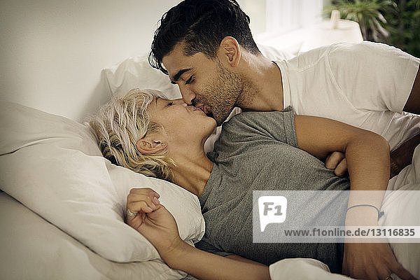 Young couple kissing on bed at home