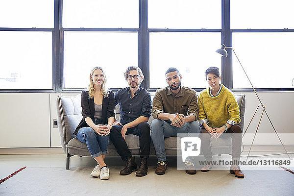 Porträt von lächelnden Geschäftsleuten  die im Büro auf dem Sofa am Fenster sitzen