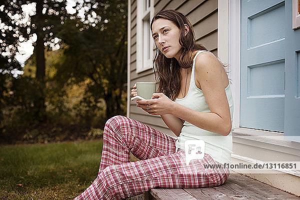 Nachdenkliche junge Frau hält Smartphone und Kaffeetasse in der Hand  während sie vor dem Haus sitzt