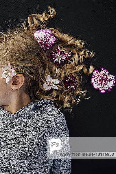 Draufsicht auf ein Mädchen mit Blumen im Haar  das auf schwarzem Hintergrund liegt
