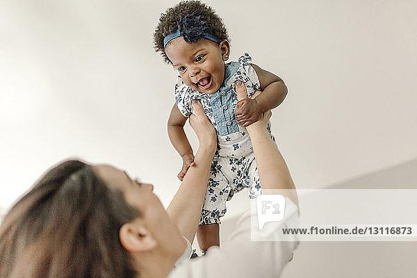 Niedriger Blickwinkel auf glückliche Mutter  die ihre Tochter zu Hause abholt