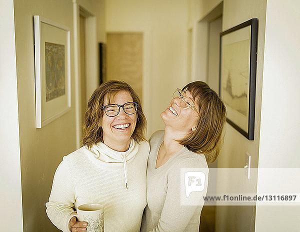 Fröhliche Schwestern stehen zu Hause im Flur