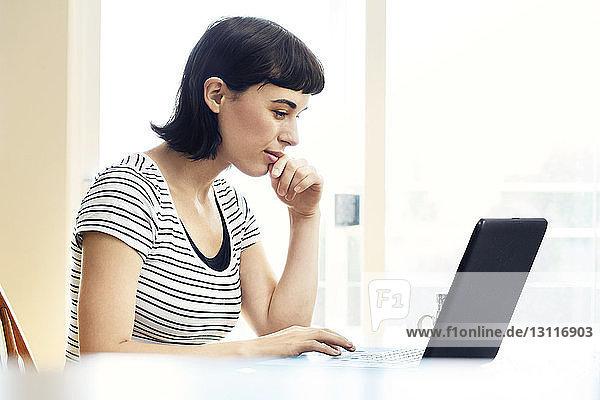 Seitenansicht einer lächelnden Frau  die einen Laptop benutzt  während sie zu Hause sitzt
