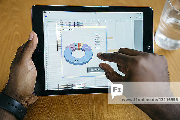 Ausgeschnittenes Bild eines Geschäftsmannes mit Tablet-Computer am Tisch
