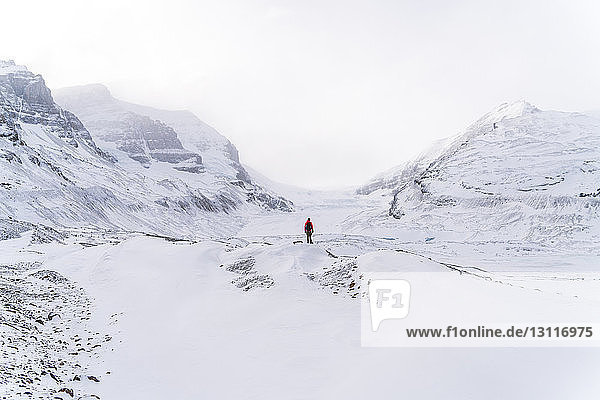 Mid distance view of hiker standing on snow covered landscape during foggy weather