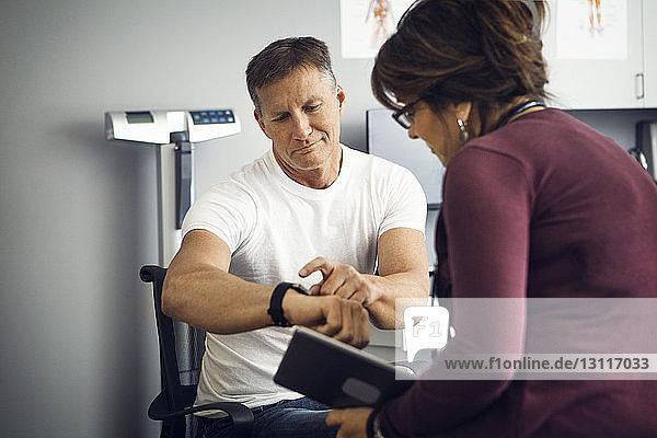 Männlicher Patient zeigt einer Ärztin in der Klinik eine Armbanduhr