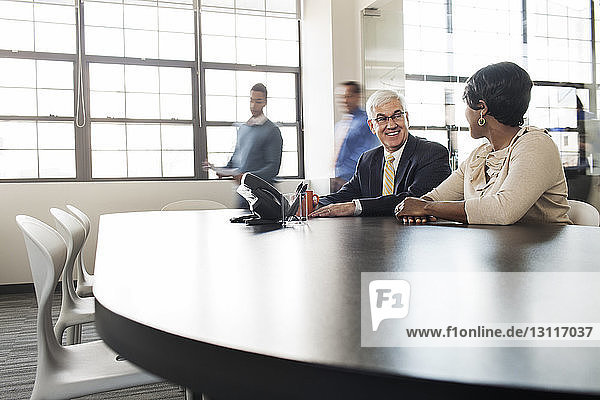 Smiling business people sitting at conference table in office