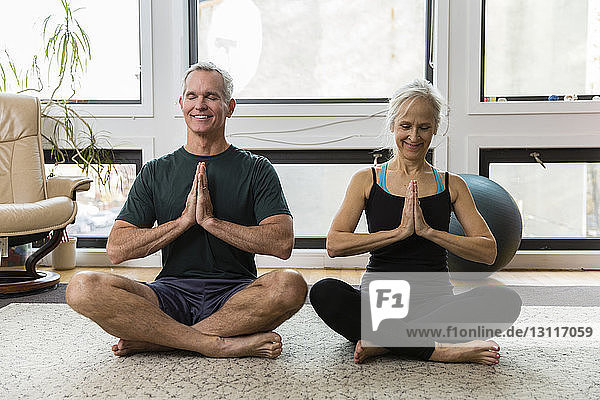 Paar in voller Länge mit gefalteten Händen meditiert  während es zu Hause Sport treibt