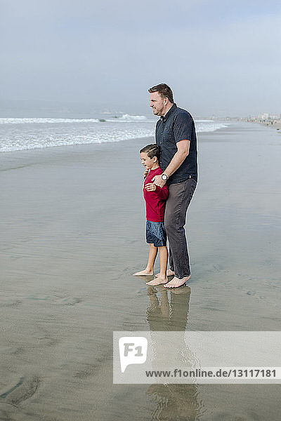 Full length of father and son looking at view while standing on shore at beach
