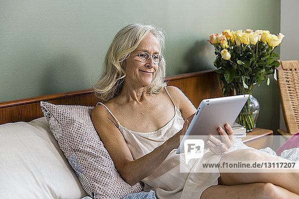 Ältere Frau benutzt Tablet-Computer am Bett zu Hause
