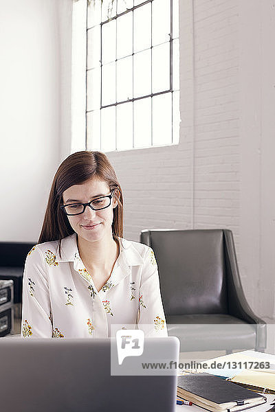 Confident businesswoman using laptop while sitting in office