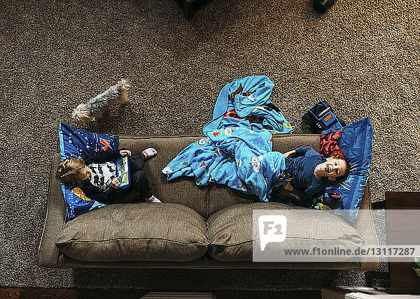 Overhead view of boys lying on sofa at home