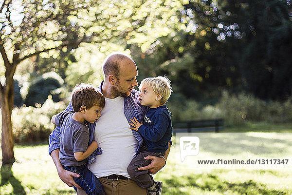 Mann trägt Söhne  während er im Park steht