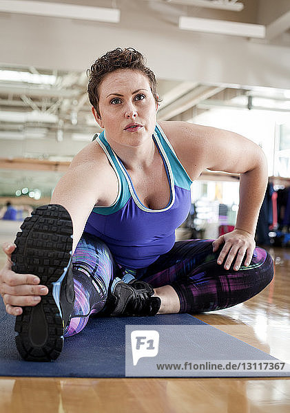 Full length of curvy woman exercising in gym