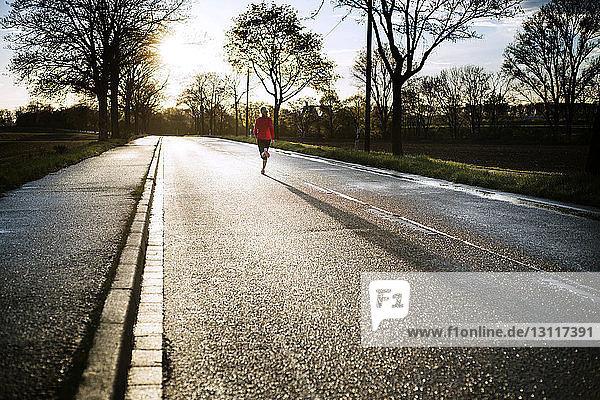 Mittelstrecke einer Frau  die bei Sonnenuntergang auf der Straße läuft