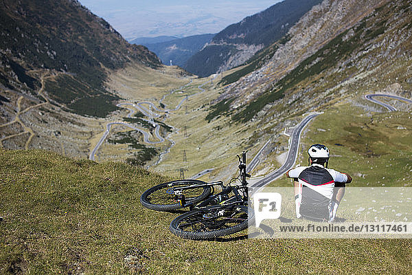 Rear view of male athlete sitting by bicycle on mountain