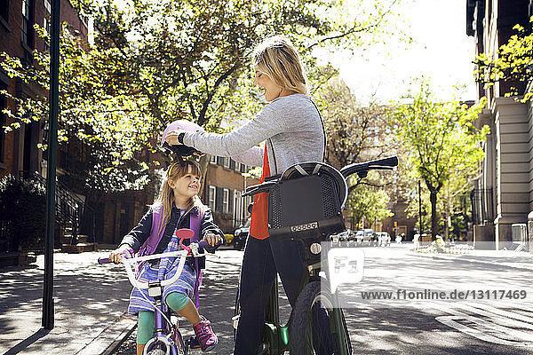 Seitenansicht einer Frau  die einen Helm auf ihre Tochter setzt  die auf der Straße Fahrrad fährt