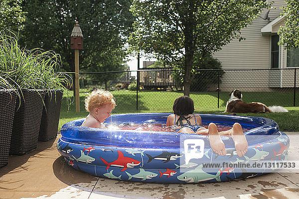 Siblings swimming in wading pool at yard