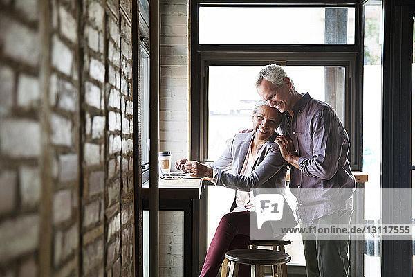 Lächelndes Paar umarmt sich an den Fenstern eines Cafés
