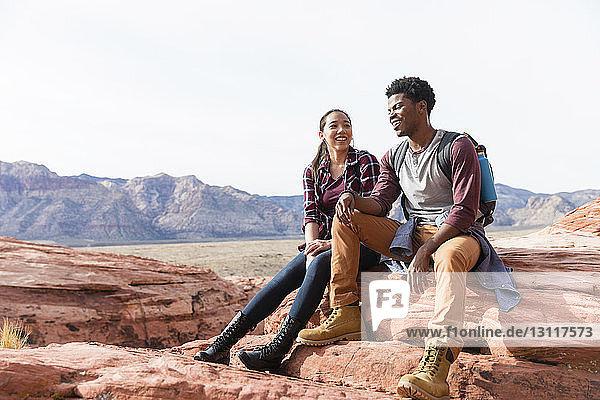 Freunde unterhalten sich  während sie bei strahlendem Sonnenschein auf Felsformationen vor klarem Himmel sitzen