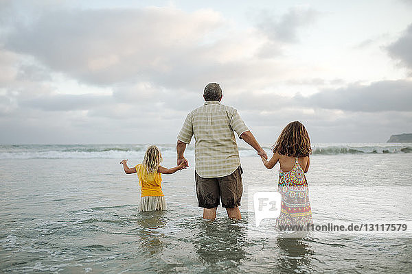 Rear view of father holding daughters hands while standing in sea against cloudy sky