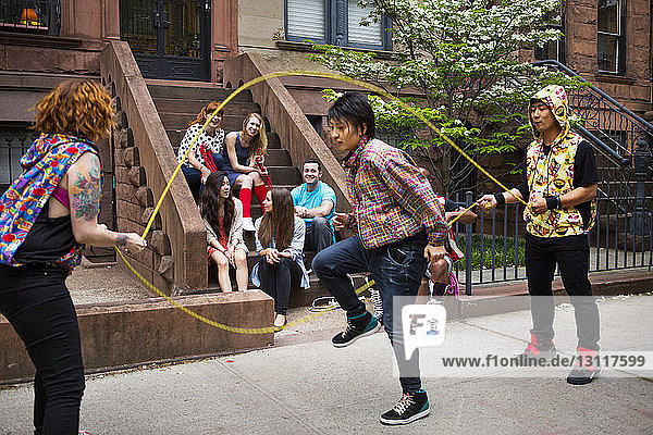 Happy friends looking at man performing double Dutch on sidewalk