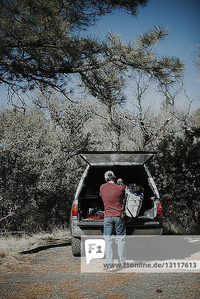 Rear view of man carrying backpack standing by off-road vehicle in forest during sunny day